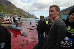 Bloody faces of the whalers following the slaughter. Photo: Julian Patterson