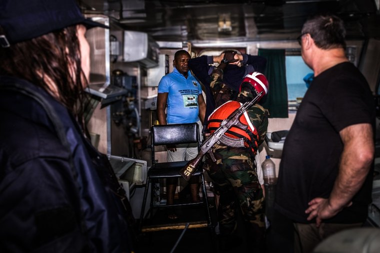 A Liberian Coast Guard sailor pats down the bridge crew of the Dzintars. Photo Melissa Romao/Sea Shepherd.
