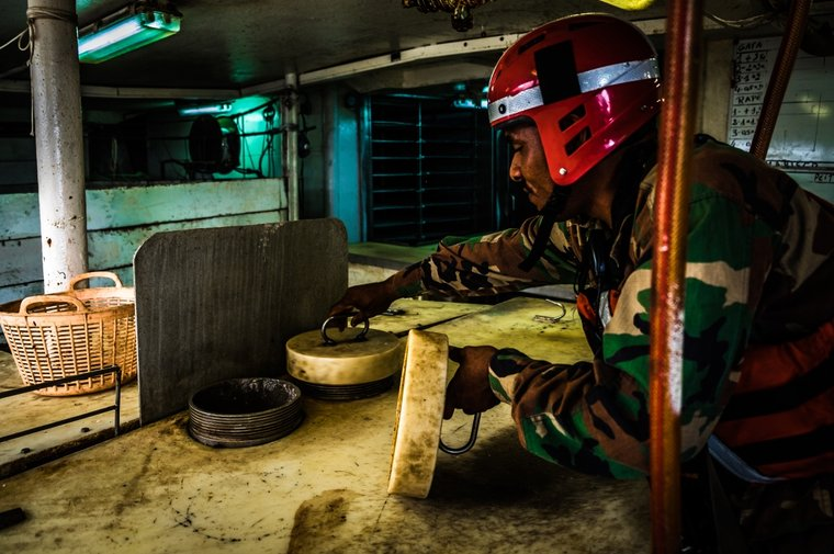 Liberian Coast Guard sailor inspects shark liver production facility. Photo by Melissa Romao/Sea Shepherd.