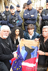 Captain Paul Watson, Lamya Essemlali, Christophe Marie, and Francois Xavier Pelletier with the body of a baby pilot whale and National Police in front of the Danish Embassy in Paris