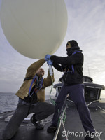 Crewmembers Larry Routledge and Ben Wilson fill a balloon with helium