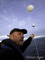 Crewmember Kevin McGinty readies a balloon for launch