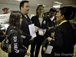 Gary Stokes and a group of Sea Shepherd volunteers and supporters speak to a Hong Kong Airlines representative.
