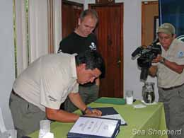 Galapagos National Park Director, Edwin Naula signs the paperwork to finalize the handover